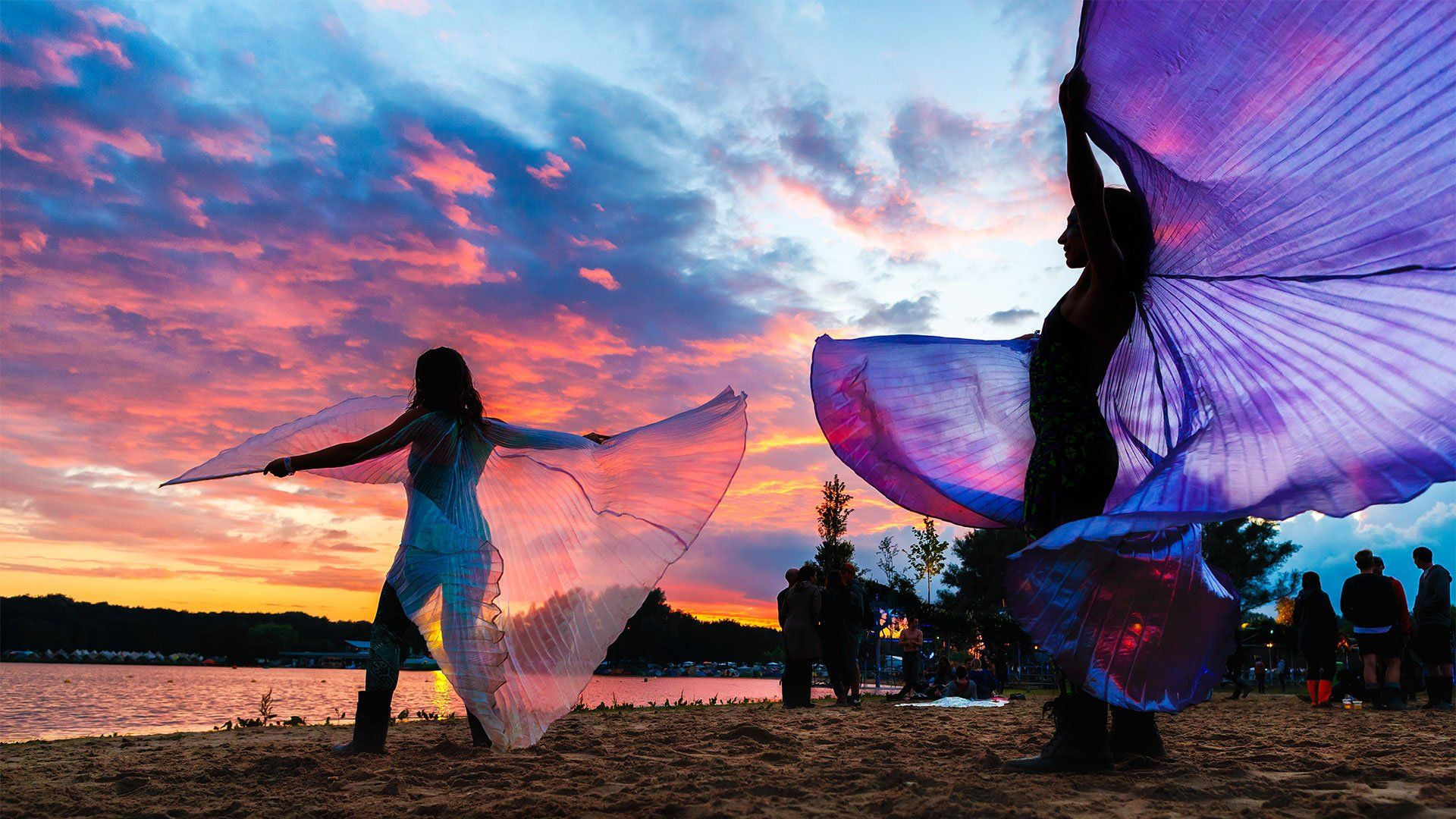 Two women twirl colourful silks at sunset. Photo by Bart Heemskerk.